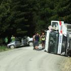 Police investigate at the scene of a head-on collision yesterday which resulted in the driver of...