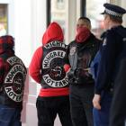 Police talk to people waiting outside the courthouse while Black Power and Mongrel Mob members...