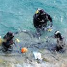 Police divers recover a number plate from Lake Wakatipu after examining the rental car that...