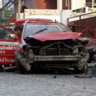 Policemen inspect a taxi damaged in an explosion in Ekamai area in central Bangkok. REUTERS/Kerek...