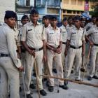 Policemen stand outside Chhattisgarh Institute of Medical Sciences hospital where several women...