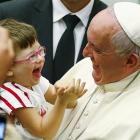 Pope Francis laughs with a child during a special audience  at the Vatican on Sunday. Photo by...