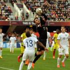 Flanked by defenders from his own team, Portugal goalie Andre Moreira takes the ball as Colombia...