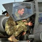 Prince Harry examines the cockpit of an Apache helicopter at Camp Bastion in Afghanistan at the...