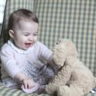 Princess Charlotte enjoys playing with a toy puppy. Photos Reuters