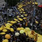 Pro-democracy protesters carrying yellow umbrellas, symbol of the Occupy Central movement, take...