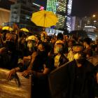Pro-democracy protesters wearing goggles and masks block a road outside the chief executive...