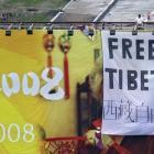 "Pro Tibet activists unfurl a ""Free Tibet"" banner and Tibetan flags on top of a Beijing Olympics..."