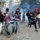 Protesters help a man affected by tear gas, during clashes with riot police near Tahrir Square in...
