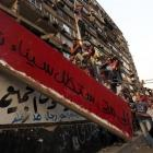Protesters pull down part of a concrete wall built in front of the Israeli embassy in Cairo....