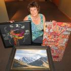 Otago Art Society president Jenny Longstaff, of Dunedin, presents examples of the art  to be...