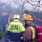 Ravensbourne man Kim Hayward checks the damage as firefighters dampen down a hedge fire on his...