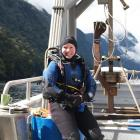 Rebecca McLeod in her drysuit before diving for samples in Fiordland. Behind her is a seafloor...