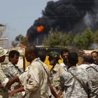 Rebels gather at an oil refinery as an LPG tank burns behind them outside the town of Brega,...