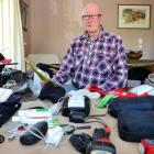 Red Cross disaster response co-ordinator Douglas Clark (71) goes through a checklist of gear...