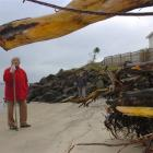 Rei and Ray Owens (in the distance) inspect the sand below their Harington Pt Rd garage, which...