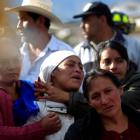 Relatives of a man react after his body was found in a landslide triggered by an earthquake, in...