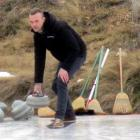 Reporter Liam Cavanagh tries curling yesterday. Photo by Joanne Herd.