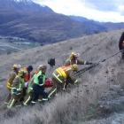 Rescue crews lift an injured passenger  to a waiting ambulance from the site of a crash where a...