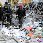 Rescue personnel walk through paper and office items in the remains of the CTV building. Photo by...