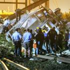 Rescue workers climb into the wreckage of the crashed train. Photo by Reuters