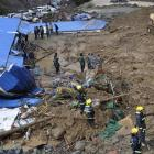 Rescuer workers at the site of a massive landslide triggered by heavy rain in Pengta Town,...