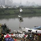 Rescuers lift part of the wreckage of TransAsia Airways plane Flight GE235 after it crash landed...