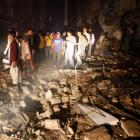 Residents and rescue workers gather at the site of a bomb blast in a residential area in Karachi....