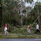 Residents of the coastal town of Yeppoon step through fallen trees alongside a damaged home after...