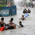 Residents wade through floodwaters brought by Typhoon Nesat in the Tanza town of Malabon city,...