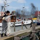 Rob Ong kisses his bride May Eng on Careys Bay wharf on Monday afternoon, just as a large fire...