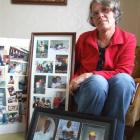 Robyn Couper with photographs of some of her Haitian friends. Photo by Sally Rae.