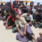 Rohingyas sit on a jetty by the  Naf River after they were arrested by Bangladeshi border guards ...