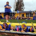 Romahapa School principal Mark Preddy and pupils spell it out in blue, gold and maroon yesterday....