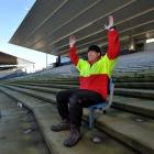 Rotarian Brendan Bearman tries out one of the last seats left in the Railway Stand at Carisbrook...
