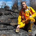 Rural Fire Officer Jamie Cowan holds one of the fireworks which caused the Queenstown Hill fire....