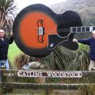Russell Kirk (right) hands over the Catlins Woodstock Festival to Kev Thompson. Photo supplied.