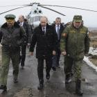 Russia's President Vladimir Putin (centre), accompanied  by Russian Defence Minister Sergei...