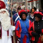 Saint Nicholas (L) is followed by his two assistants called 'Zwarte Piet' (Black Pete) during a...