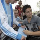 Samir Nasri signs autographs as he is greeted by fans outside Manchester City's Etihad Stadium in...
