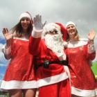 Santa Claus  is joined by two elves, Mikaela Young (left) and Alice Kingan, both of Oamaru, at...