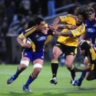 Highlander's star no 8 Steven Setephano is collared by Hurricanes winger Ma'a Nonu.  Photo by Craig Baxter