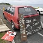 Signs arguing for the reopening of John Wilson Ocean Dr, lean against a car parked at the...