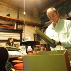 Simon Knight fills cardboard boxes with his father's collections. Photo by Craig Baxter.