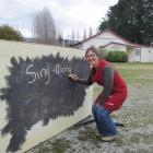Sing-along organiser Julie Davie creates a sign outside the Earnscleugh Hall. Photo by Sarah...
