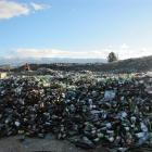 Sione Ah Mann sorts through the clean glass, recently bought in by the recycling truck. In the...