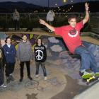 Skateboarder Chey Grace (21) shows his skill at the Dunedin Skateboard Park watched by (from left...