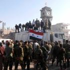 Soldiers loyal to the Syrian regime and civilians gather as they place the Syrian national flag...