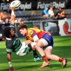 South Canterbury halfback Sekope Maea (left) tries to offload in the tackle of North Otago...