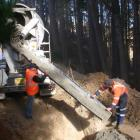 SouthRoads crew Ian Schroeder (left) and Daryl Falconer pour concrete into a hole in Ridge Rd,...